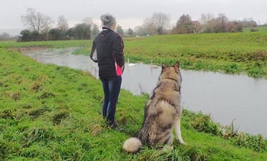 dog and owner sat by river